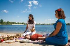 Красивый женский получая массаж энергии ядровый с массажем шаров и тела петь на речном береге Стоковые Изображения RF