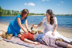 Красивый женский получая массаж энергии ядровый с массажем шаров и тела петь на речном береге Стоковое Фото