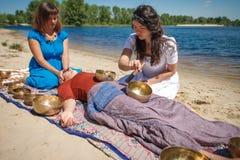 Красивый женский получая массаж энергии ядровый с массажем шаров и тела петь на речном береге Стоковые Фото
