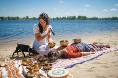 Красивый женский получая массаж энергии ядровый с шарами петь на речном береге Стоковое Изображение