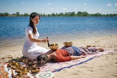 Красивый женский получая массаж энергии ядровый с шарами петь на речном береге Стоковое Изображение RF
