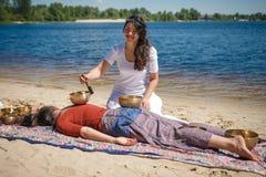 Красивый женский получая массаж энергии ядровый с шарами петь на речном береге Стоковое Фото