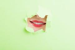 Красивый женский рот показывая улыбку через сорванный картон Стоковое Изображение