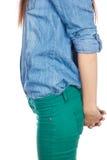 Красивый, женщина брюнет стоя на белой предпосылке в рубашке джинсовой ткани Стоковая Фотография RF