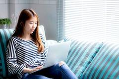 Красивый женщины портрета молодой азиатской используя компьтер-книжку для отдыха на софе в живущей комнате Стоковые Изображения