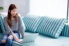Красивый женщины портрета молодой азиатской используя компьтер-книжку для отдыха на софе в живущей комнате Стоковое Изображение RF