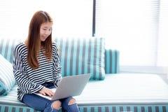 Красивый женщины портрета молодой азиатской используя компьтер-книжку для отдыха на софе в живущей комнате, работе девушки онлайн Стоковое Фото