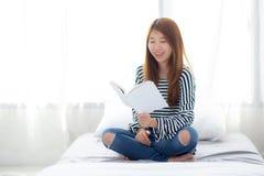 Красивый женщины портрета молодой азиатской ослабьте сидя книгу чтения на спальне дома Стоковое Изображение RF