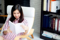 Красивый женщины портрета молодой азиатской ослабьте сидя книгу чтения в живущей комнате Стоковые Изображения RF