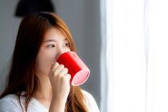 Красивый женщины портрета молодой азиатской с acup питья предпосылки окна занавеса кофе стоящей Стоковые Изображения