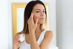 Красивый заботить молодой женщины ее кожи стоя близко зеркало в ванной комнате стоковое фото