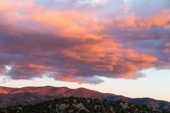 Красивый заход солнца бросает пурпурные и оранжевые цвета на облаках и горах около Санта-Фе, Неш-Мексико стоковые фотографии rf