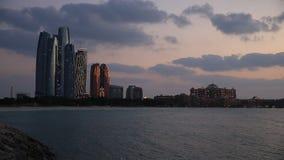 Красивый заход солнца в Абу-Даби с современными зданиями освещенными вверх видеоматериал
