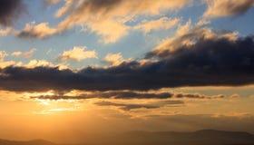 Красивый заход солнца на небе Солнце золота облегчает облака над горами Солнце на левой стороне Стоковое фото RF