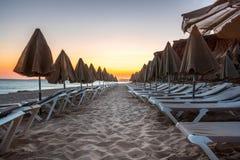 Красивый заход солнца в Алгарве Португалии Пляж и скалы с закрытыми зонтиками солнца и sunbeds Стоковые Фото