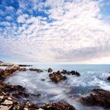 Красивый заход солнца заволакивает над камнями моря близко для того чтобы пристать к берегу Стоковые Фотографии RF