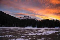 Красивый заход солнца зимы с оранжевыми горами и лесом Альпов неба и снега облака в зоне Engadine Стоковые Изображения RF