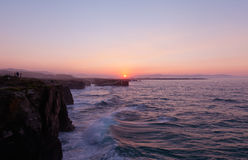 Красивый заход солнца и каменные своды на Playa de las Catedrales Стоковая Фотография