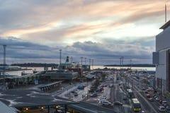Красивый заход солнца и портовая зона показывая занятый современный промышленный порт, транспорт, мировую торговлю, Хельсинки, Фи Стоковое Фото