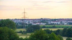 Красивый заход солнца над полем и маленьким городом в Германии Стоковые Изображения