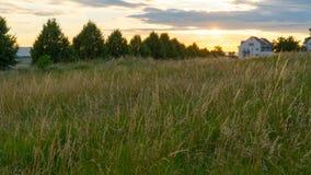 Красивый заход солнца над полем и маленьким городом в Германии Стоковые Фото