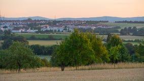 Красивый заход солнца над полем и маленьким городом в Германии Стоковые Изображения RF