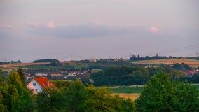 Красивый заход солнца над полем и маленьким городом в Германии Стоковое Изображение