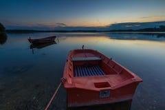 Красивый заход солнца озера с шлюпками рыболова Стоковые Изображения