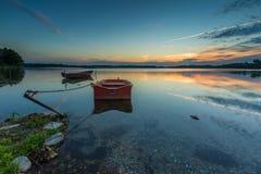 Красивый заход солнца озера с шлюпкой рыболова Стоковое Изображение RF