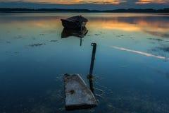 Красивый заход солнца озера с шлюпкой рыболова Стоковые Изображения