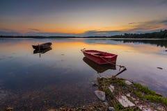 Красивый заход солнца озера с шлюпкой рыболова Стоковое фото RF