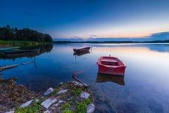 Красивый заход солнца озера с шлюпкой рыболова Стоковые Фото