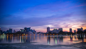 Красивый заход солнца около озера осветил вверх с светами города Куалаа-Лумпур Стоковая Фотография
