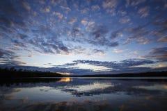 Красивый заход солнца отражая с озера Стоковое Изображение RF