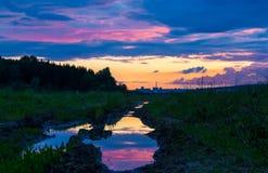 Красивый заход солнца отраженный в лужице Стоковые Фотографии RF