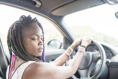 Красивый задумчивый африканский женский водитель сидя в автомобиле стоковое изображение rf