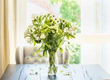 Красивый зеленый пук цветков с падая лепестками в стеклянной вазе на таблице в солнечной живущей комнате на окне Стоковое Изображение RF