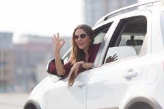 Красивый знак о'кей показа дамы от ее автомобиля Стоковая Фотография