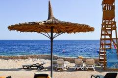 Красивый зонтик в форме шляпы в форме шляпы и спасение возвышаются против фона loungers солнца, голубого соли Стоковые Изображения