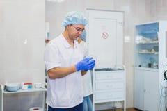 Красивый зрелый хирург в голубых медицинских носке и маске кладет на медицинские перчатки на операционной Стоковая Фотография