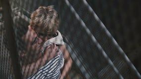 Красивый испанский человек и кавказская женщина стоя и обнимая на металлических лестницах улицы города, взгляде через загородку сток-видео
