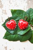 Красивый и вкусный десерт в форме сердца лежит на зеленых листьях на старой деревянной предпосылке Стоковая Фотография