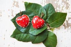 Красивый и вкусный десерт в форме сердца лежит на зеленых листьях на старой деревянной предпосылке Стоковое Изображение