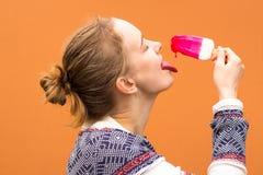 Красивый и маленькая девочка ест розовое мороженое оттенка и наслаждается Она улавливает падение расплавленного мороженого с ее я стоковое изображение rf