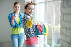 Красивый и молодая женщина делая чистку дома стоковое фото rf