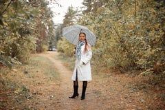 Красивый кавказец средн-постарел женщина с красными волосами с зонтиком в парке на пасмурный день осени стоковая фотография rf