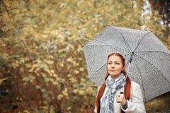 Красивый кавказец средн-постарел женщина с красными волосами с зонтиком в парке на пасмурный день осени стоковое изображение rf