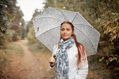 Красивый кавказец средн-постарел женщина с красными волосами с зонтиком в парке на пасмурный день осени стоковые изображения rf