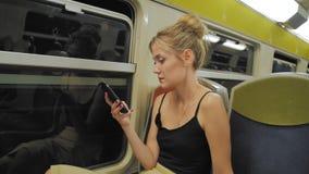 Красивый кавказский женский турист едет поезд через тоннель Вне окна света двигают Использует мобильное сток-видео
