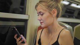 Красивый кавказский женский турист едет поезд через тоннель Вне окна света двигают Использует мобильное видеоматериал
